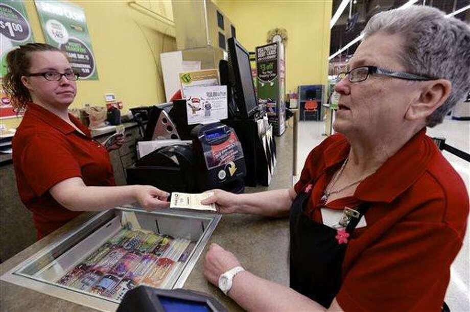 Sharon Brickey, right, purchases a Powerball ticket from Tiffany Enders, left, at a Baker's supermarket in Omaha, Neb., Wednesday, May 15, 2013. Enders had recently sold a million dollar Powerball ticket at the store. After weeks of rolling without a winner, the Powerball jackpot has once again ballooned in time for its Wednesday drawing, an estimated $360 million jackpot considered the third largest Powerball jackpot and the seventh largest jackpot in history. (AP Photo/Nati Harnik) Photo: AP / AP