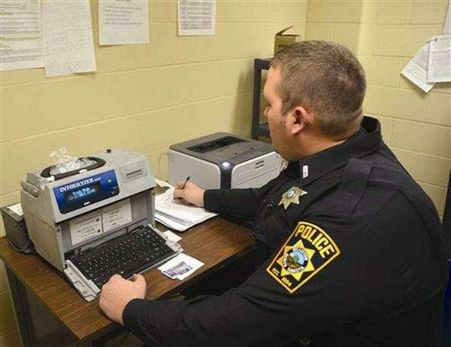 Williston Police Officer Walter Hall operates the Intoxilyzer 8,000 at the jail to determine a suspect's blood alcohol level after a DUI arrest. Hall said the police department's strategy of increasing presence near local bars around closing time has improved safety and promoted officers' communication with business owners and the public. AP Photo/Williston Herald, Jenna Ebersole Photo: AP / Williston Herald