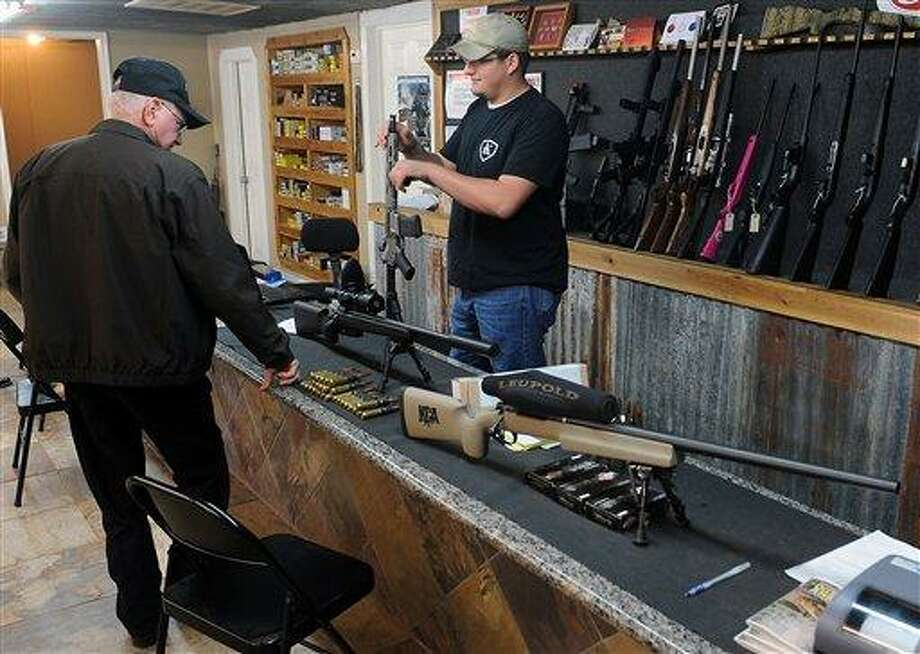 Clerk Lance McCoy, right, shows a variety of weapons, including an AR-15 style semi-automatic at Kizer Guns and Ammo near Nacogdoches, Texas. As talk and support grows both in Congress and in public opinion for a ban on the so-called assault rifles, the most popular rifle sold in America and the same type used in the Newtown, Conn., school shootings, calls from prospective buyers around the state have soared, McCoy said. AP Photo/The Daily Sentinel, Andrew D. Brosig Photo: ASSOCIATED PRESS / AP2012