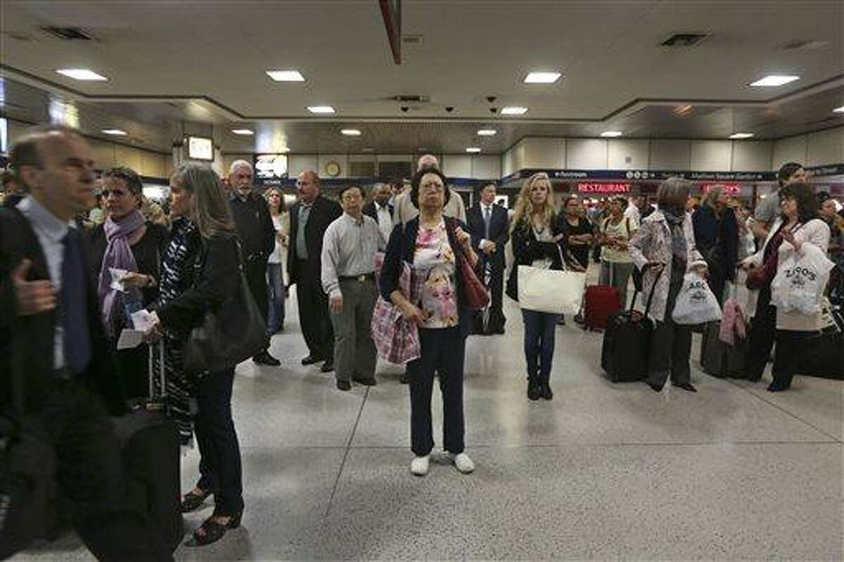 This May 9, 2013 photo shows evening rush hour commuters inspecting the train information board inside Penn Station in New York. The busiest passenger train station in the United States, gateway to the biggest city in the nation, is a 1960s-era, utilitarian labyrinth built in what is essentially the basement of Madison Square Garden. Two decades after ambitious plans were unveiled to improve Penn Station while expanding it into the massive Beaux Arts post office building across the street, there are few visible signs of change. (AP Photo/Mary Altaffer)