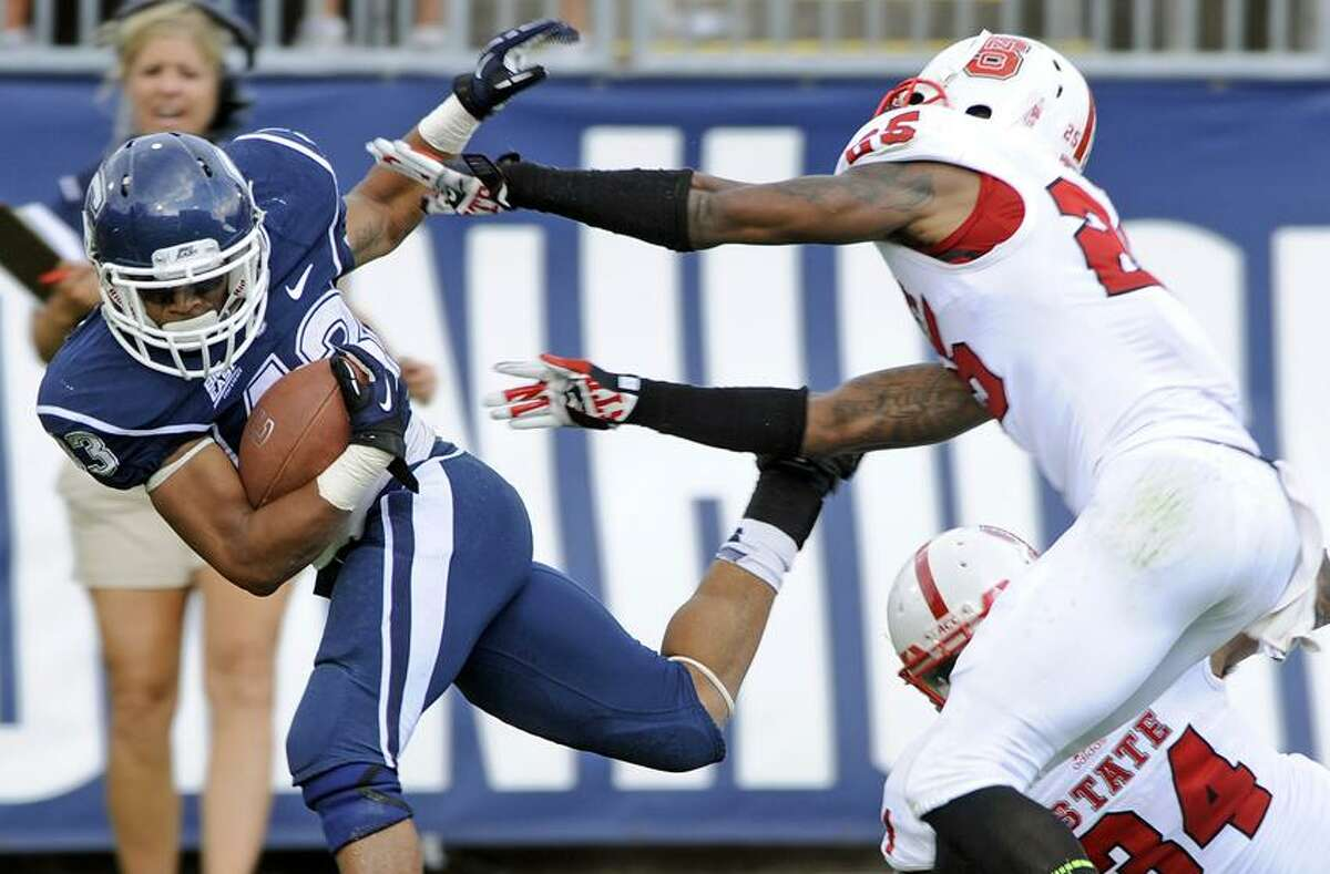 Connecticut's Lyle McCombs, left, is pushed out of bounds by North Carolina State's Dontae Johnson during the second half of North Carolina's 10-7 victory in an NCAA college football game in East Hartford, Conn., on Saturday, Sept. 8, 2012. (AP Photo/Fred Beckham)