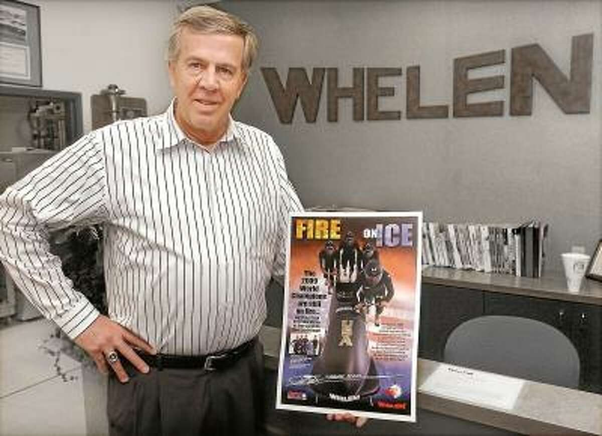 Phil Kurze, vice president at Whelen Engineering in Chester and president of the Bo0Dyn Bobsled Project displays a poster of the Night Train USA Team who won its first gold medal in more than 60 years. Catherine Avalone