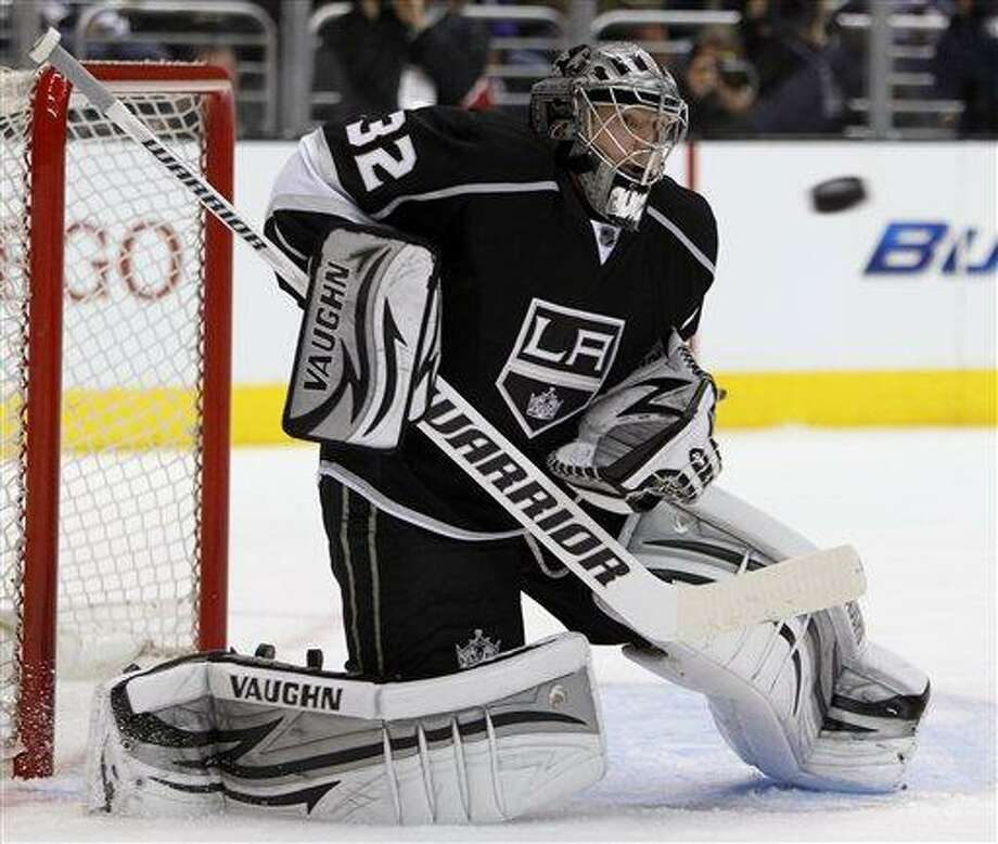 Los Angeles Kings goalie Jonathan Quick (32) keeps his eyes on the puck to make a stop against the Vancouver Canucks during the first period of Game 3 in a first-round NHL Stanley Cup playoff series in Los Angeles, Sunday, April 15, 2012.  (AP Photo/Alex Gallardo) Photo: AP / FR170211 AP