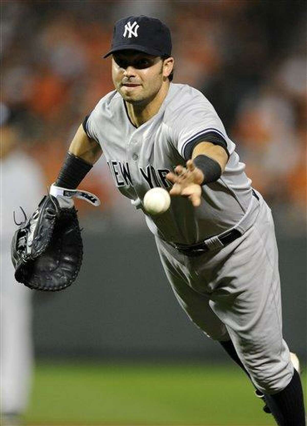 New York Yankees first baseman Nick Swisher makes a throw to first to put out Baltimore Orioles' Nick Markakis during the eighth inning of a baseball game, Thursday, Sept. 6, 2012, in Baltimore. The Orioles won 10-6. (AP Photo/Nick Wass)