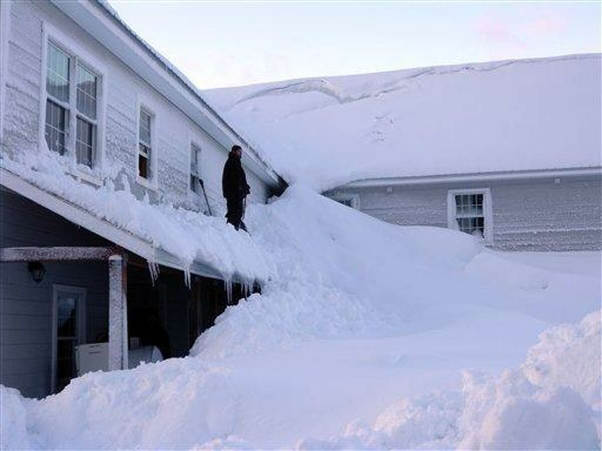 In this Jan. 7 photo provided by the Alaska Division of Homeland Security and Emergency Management, a man stands on the porch roof of a house buried in snow in the fishing town of Cordova, Alaska. Residents have turned to the state to help them dig out of massive snow levels that have collapsed roofs, triggered avalanches and even covered doors, trapping some people in their homes. Associated Press