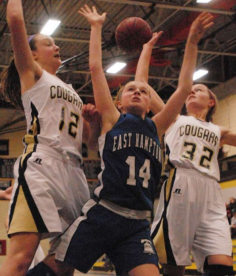 Catherine Avalone/The Middletown Press East Hampton freshman guard Morgan Slossberg is fouled during a layup by H-K sophomores Jessica Kasper (12) and Hallie Serbent (10) Friday night in Higganum. H-K defeated the Bellringers 47-33.