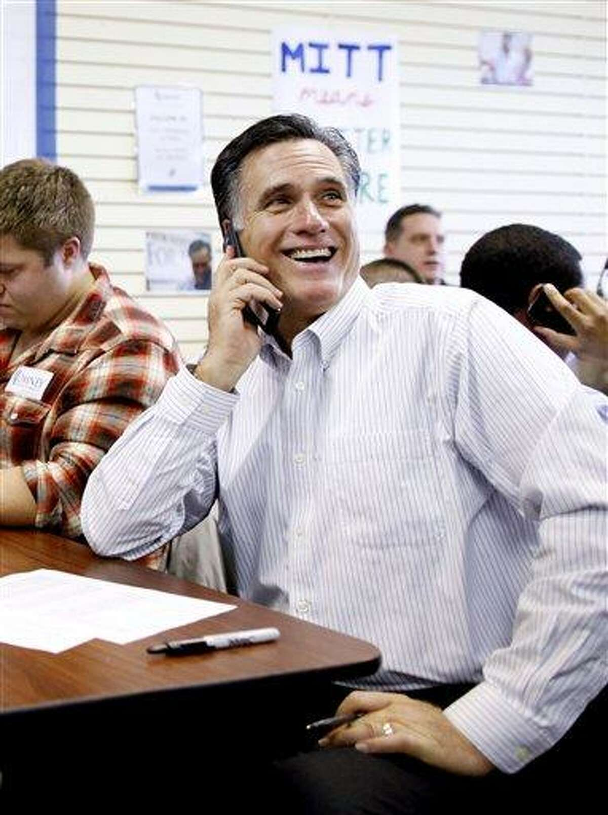 Republican presidential candidate and former Massachusetts Gov. Mitt Romney sits with volunteers and calls likely voters ahead of Tuesday's primary election in Manchester, N.H. Associated Press
