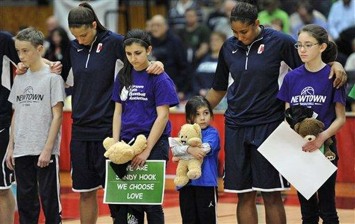FILE - In this Dec. 22, 2012 file photo, Connecticut's Caroline Doty, second from left, and Kaleena Mosqueda-Lewis, second from right, stand with children from Newtown's Youth Basketball Association during a ceremony for the victims of the Sandy Hook Elementary School shooting before an NCAA women's college basketball in West Hartford, Conn. Since the shooting tragedy on Dec. 14, 2012, athletes from across the sports world have done their part to help make Newtown children smile again. (AP Photo/Jessica Hill, File)