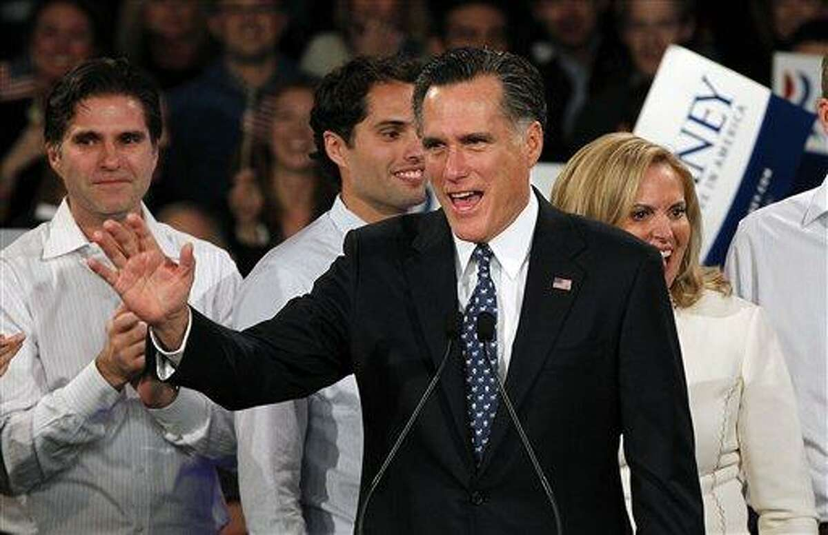 Former Massachusetts Gov. Mitt Romney waves to supporters at the Romney for President New Hampshire primary night rally at Southern New Hampshire University in Manchester, N.H., Tuesday, Jan. 10, 2012. Behind Romney are his sons Tagg and Craig and his wife Ann. (AP Photo/Elise Amendola)
