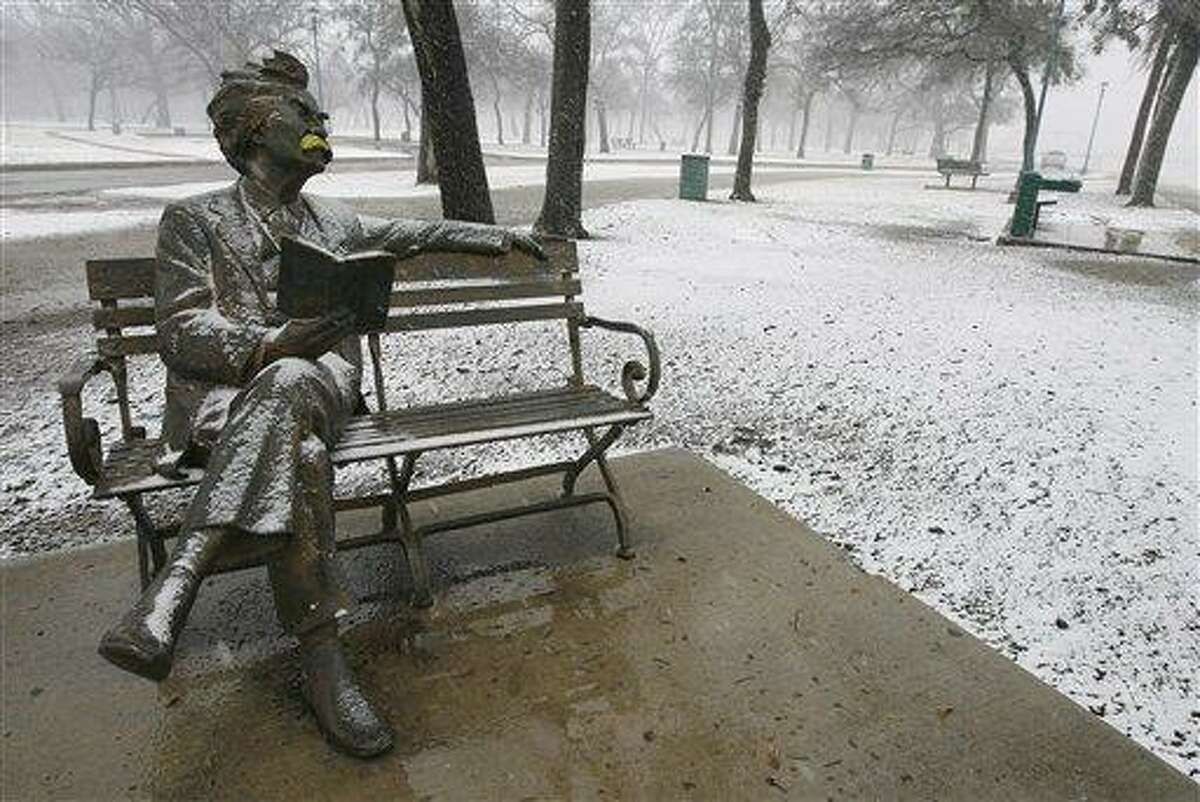 Snow falls on the Mark Twain statue in Trinity Park in Fort Worth, Texas on Christmas Day, 2012. (AP Photo/The Fort Worth Star-Telegram, Ben Noey Jr.)