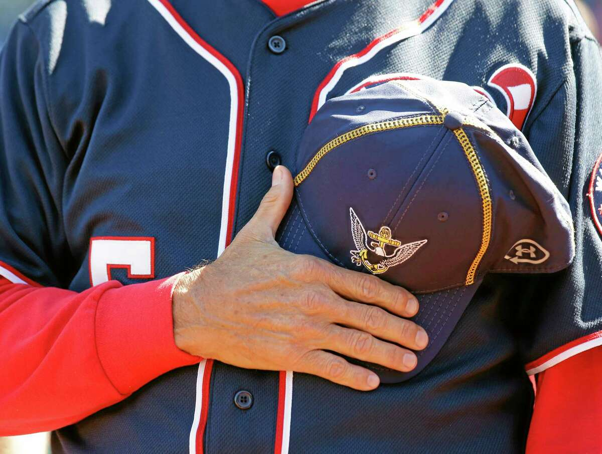 Washington manager Davey Johnson holds a Navy hat over his heart during a moment of silence before the Nationals' game against the Atlanta Braves at Nationals Park on Tuesday in Washington. The Nationals wore Navy hats, presented to them before the game, by Adm. James A. Winnefield, vice-chairman of the Joint Chiefs of Staff, to honor those killed and injured in the attack Monday at the nearby Washington Navy Yard.