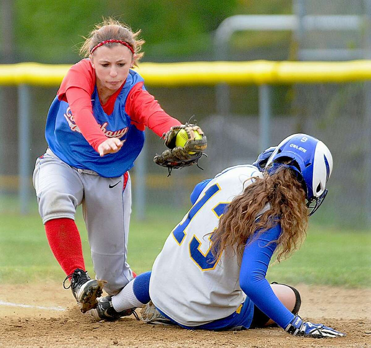Catherine Avalone/The Middletown PressCoginchaug second baseman Dina Canalia looks to tag H-K's Sam Waskowitz at first Wednesday in Durham. H-K won, 6-3.