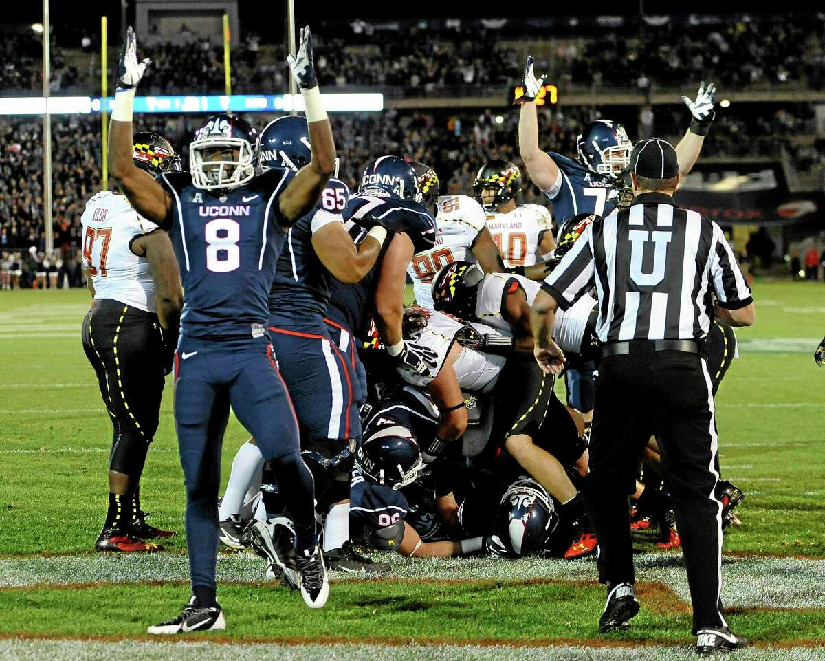 UConn wide receiver Shakim Phillips (8) celebrates a touchdown by running back Lyle McCombs during the Huskies' loss to Maryland Saturday at Rentschler Field in East Hartford.