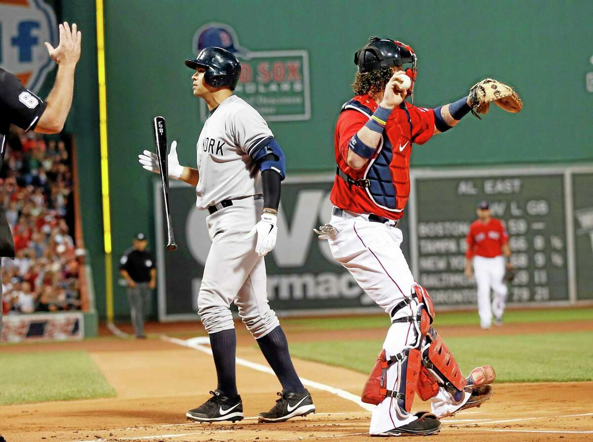 The New York Yankees' Alex Rodriguez walks away from the plate after striking out as Red Sox catcher Jarrod Saltalamacchia gets ready to fire the ball around the horn in Friday's game at Fenway Park.