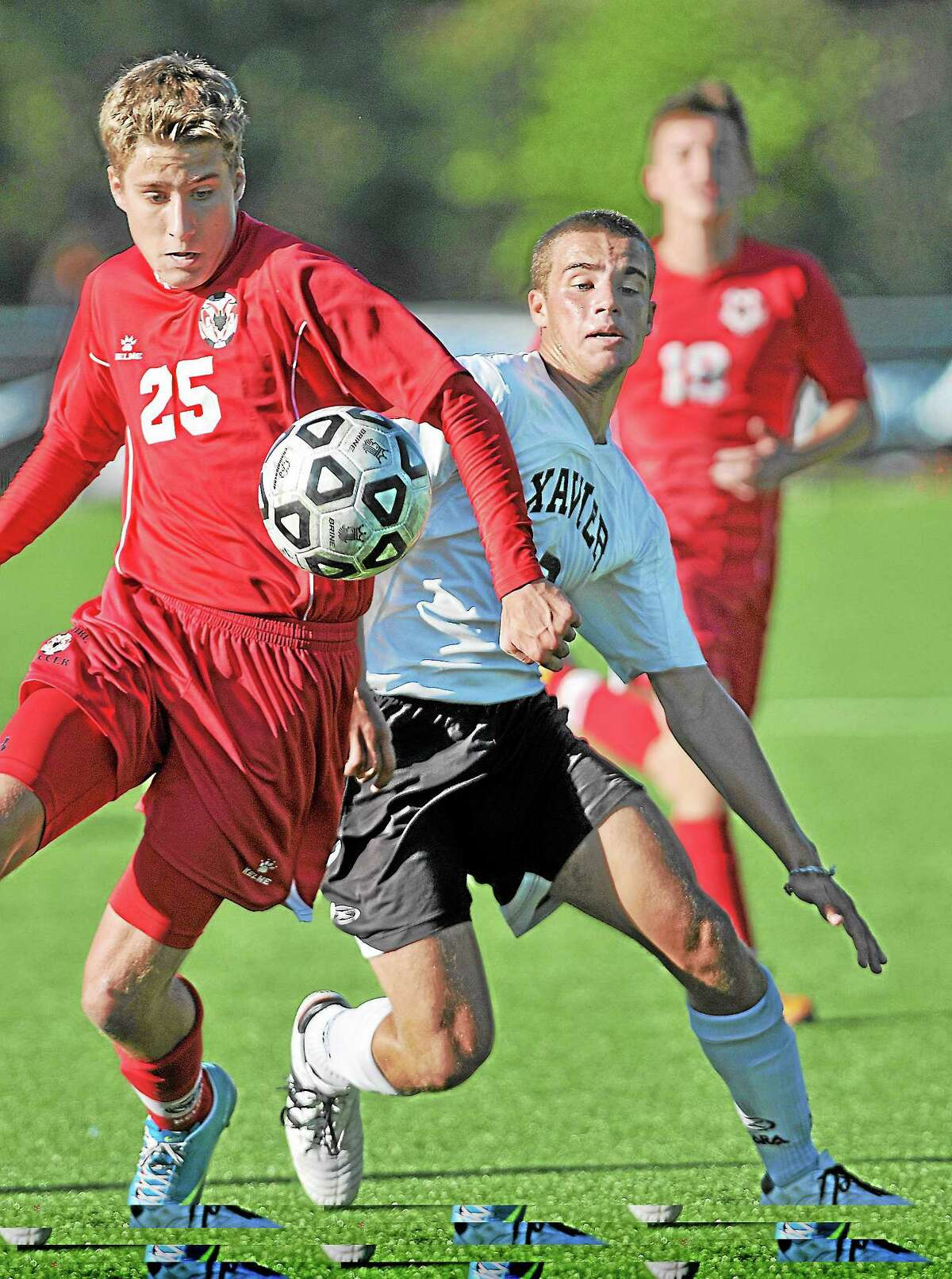 Catherine Avalone — The Middletown Press Xavier's Brendan Charton battles Griffin Andes near the Cheshire goal in the second half of Tuesday's game at TD Bank Oakwood Soccer Park in Portland. The game ended in a 0-0 tie.