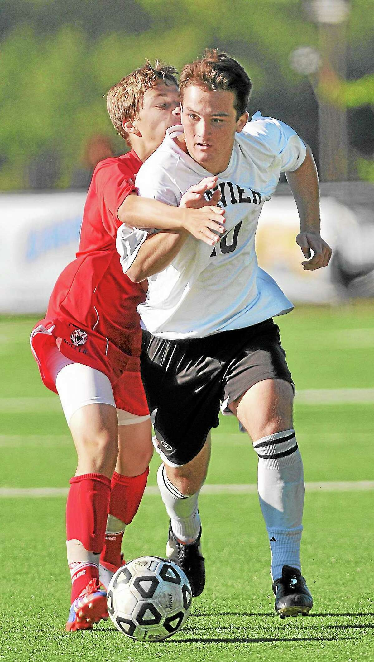 Xavier's Brendan Burtler moves the ball around Cheshire's Eric Dishnica in the second half of Tuesday's game at TD Bank Oakwood Soccer Park in Portland. The game ended in a 0-0 tie.