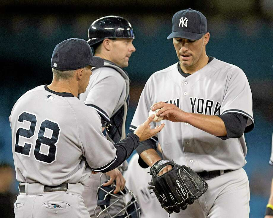 Frank Gunn  — The Canadian Press/The Associated Press New York Yankees manager Joe Girardi, left, pulls starting pitcher Andy Pettitte during the seventh inning against the Toronto Blue Jays. Photo: AP / The Canadian Press