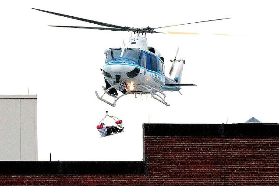A U.S. Park Police helicopter removes a man in a basket from the Washington Navy Yard Monday, Sept. 16, 2013.    Earlier in the day, the U.S. Navy said it was searching for an active shooter at the Naval Sea Systems Command headquarters, where about 3,000 people work.  The exact number of people killed and the conditions of those wounded was not immediately known.  (AP Photo/Jacquelyn Martin) Photo: ASSOCIATED PRESS / AP2013