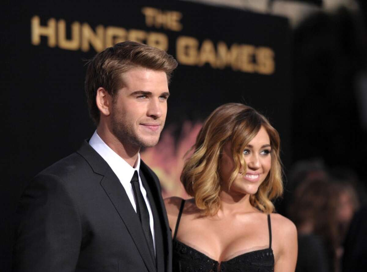 """LOS ANGELES, CA - MARCH 12: Actors Liam Hemsworth and Miley Cyrus attend """"The Hunger Games"""" Los Angeles Premiere at Nokia Theatre at LA Live on March 12, 2012 in Los Angeles, United States. (Photo by John Shearer/WireImage)"""