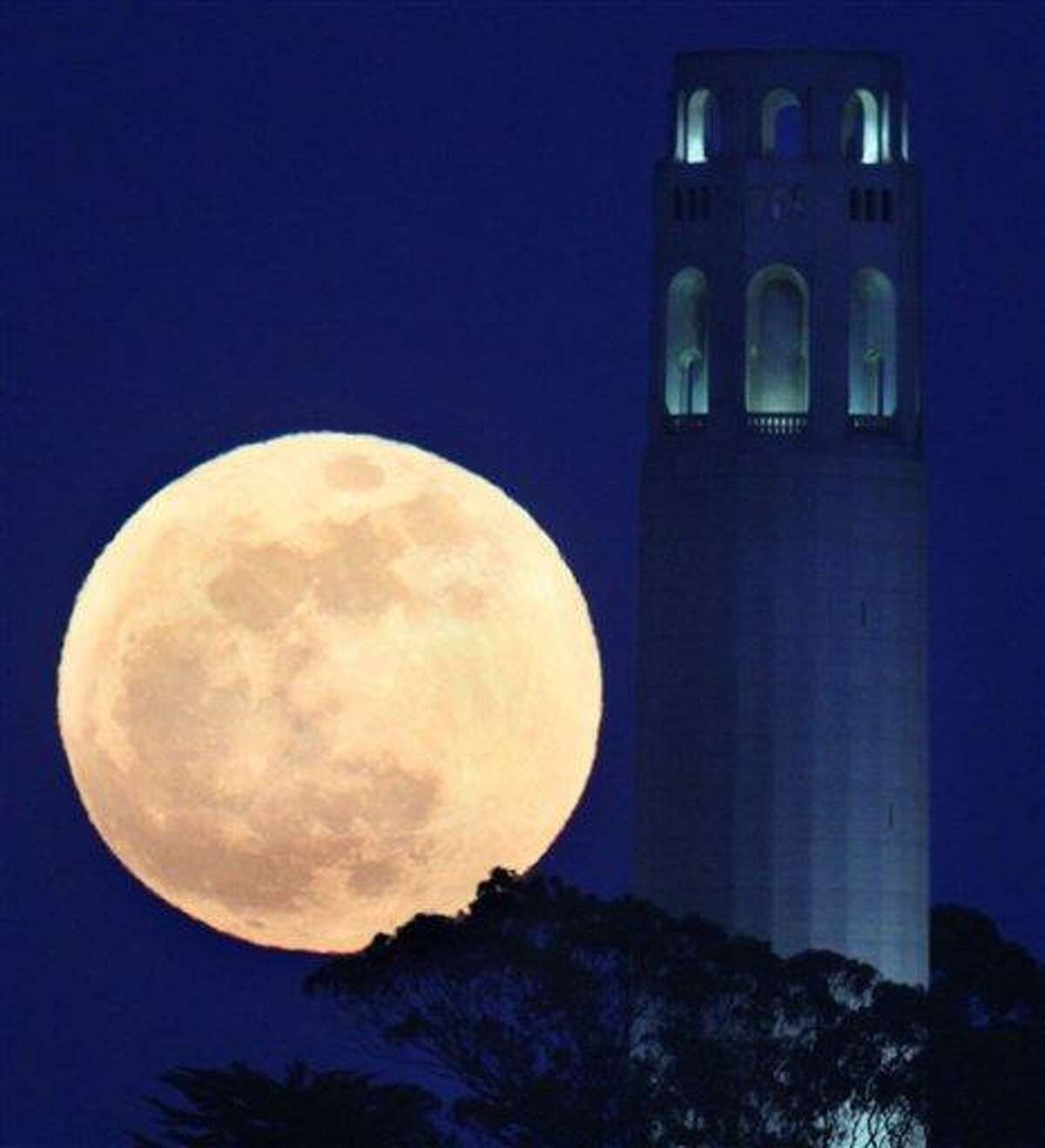 The May's full moon rises next to San Francisco Coit Tower in San Francisco Saturday. Associated Press