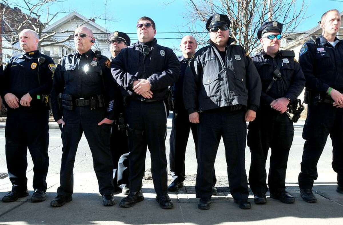 Members of area police departments watch Norwich Police Officer Johathan Ley leave Yale-New Haven Hospital on 1/10/2013. Ley suffered a gunshot wound in a standoff on Monday.Photo by Arnold Gold/New Haven Register AG0480A