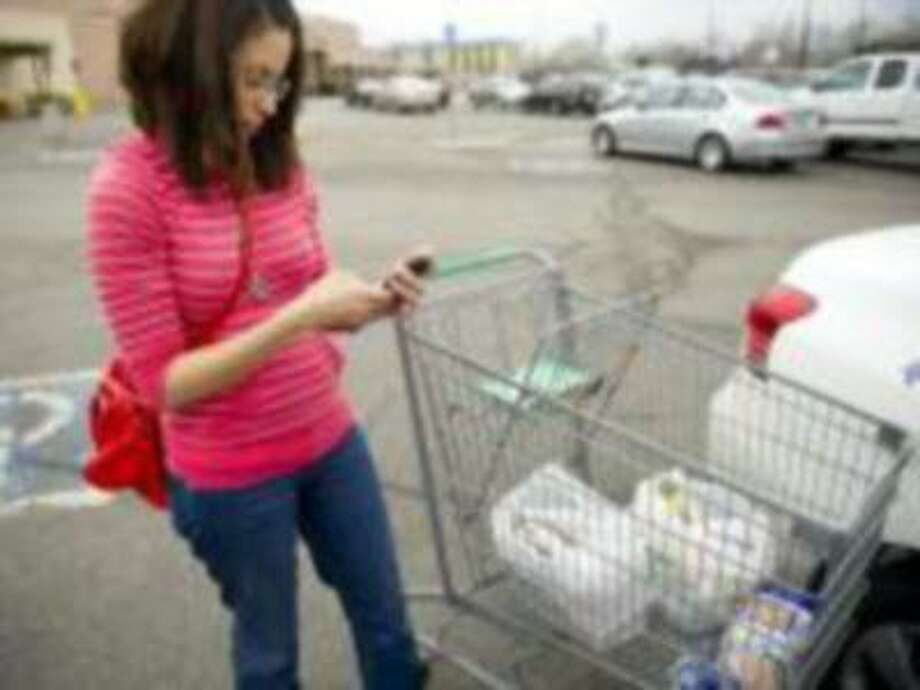 After using her smartphone to look for deals while grocery shopping, Alma Sauseda loads her car up at a Denver market. (Cyrus McCrimmon/The Denver Post) Photo: DP / Copyright - 2013 The Denver Post, MediaNews Group.