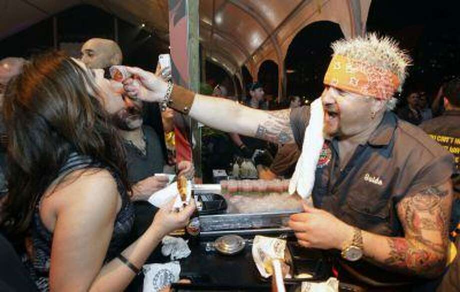"Guy Fieri, right, feeds Rachael Ray, left, at the South Beach Wine and Food Festival's Burger Bash, Friday, Feb. 22, 2013, in Miami Beach, Fla. The mass exodus from rockland to foodland has helped chisel a phrase into our collective marble: ""Chefs are the new rock stars."" Photo: ASSOCIATED PRESS / AP2013"