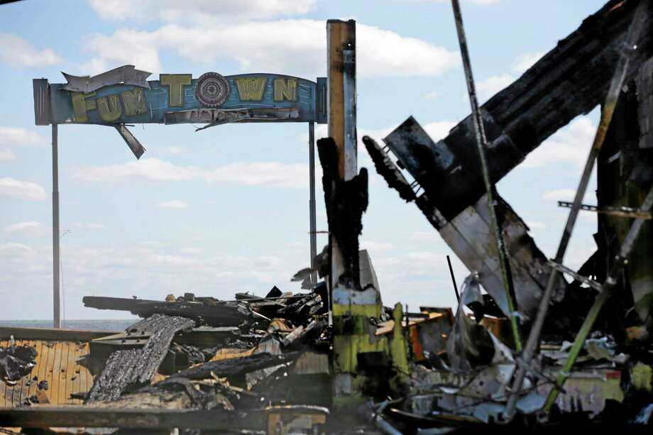 The sign for Funtown Pier stands above charred rubble in Seaside Park, N.J., Tuesday, Sept. 17, 2013, after a fire last Thursday that started near a frozen custard stand in Seaside Park,  quickly spread north into neighboring Seaside Heights. More than 50 businesses in the two towns were destroyed. The massive boardwalk fire in New Jersey began accidentally, the result of an electrical problem, an official briefed on the investigation said Tuesday. (AP Photo/Mel Evans) Photo: AP / AP
