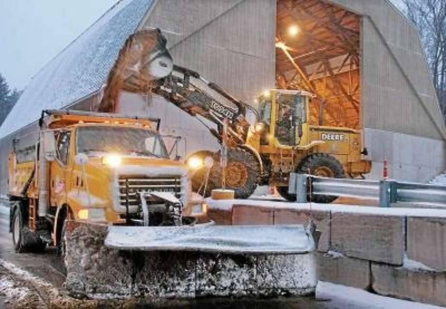John Hood refills sand and salt for Joe Barone Tuesday evening at Middletown Public Works on the corner of Washington and Butternut Streets.                 Jennifer Sprague