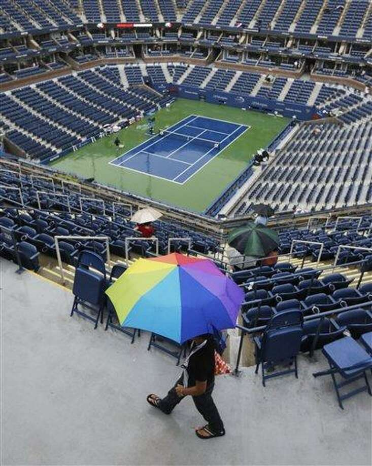 Tennis fans use umbrellas during a rain delay for a match between Victoria Azarenka, of Belarus, and Samantha Stosur, of Australia, in the quarterfinals of the 2012 US Open tennis tournament,  Tuesday, Sept. 4, 2012, in New York. (AP Photo/Mike Groll) Photo: ASSOCIATED PRESS / AP2012