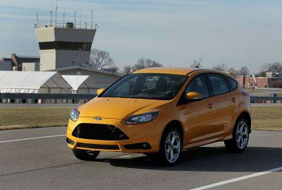 """The 2013 Ford Motor Co. Focus ST vehicle in a color called """"tangerine scream"""" sits parked on the test track at the company's Dearborn Development Center in Dearborn, Michigan, U.S., on Thursday, Dec. 13, 2012. Ford's Dearborn Development Center opened in 2006 after a $43 million transformation of the company's historic Dearborn Proving Grounds facility. Photographer: Jeff Kowalsky/Bloomberg"""