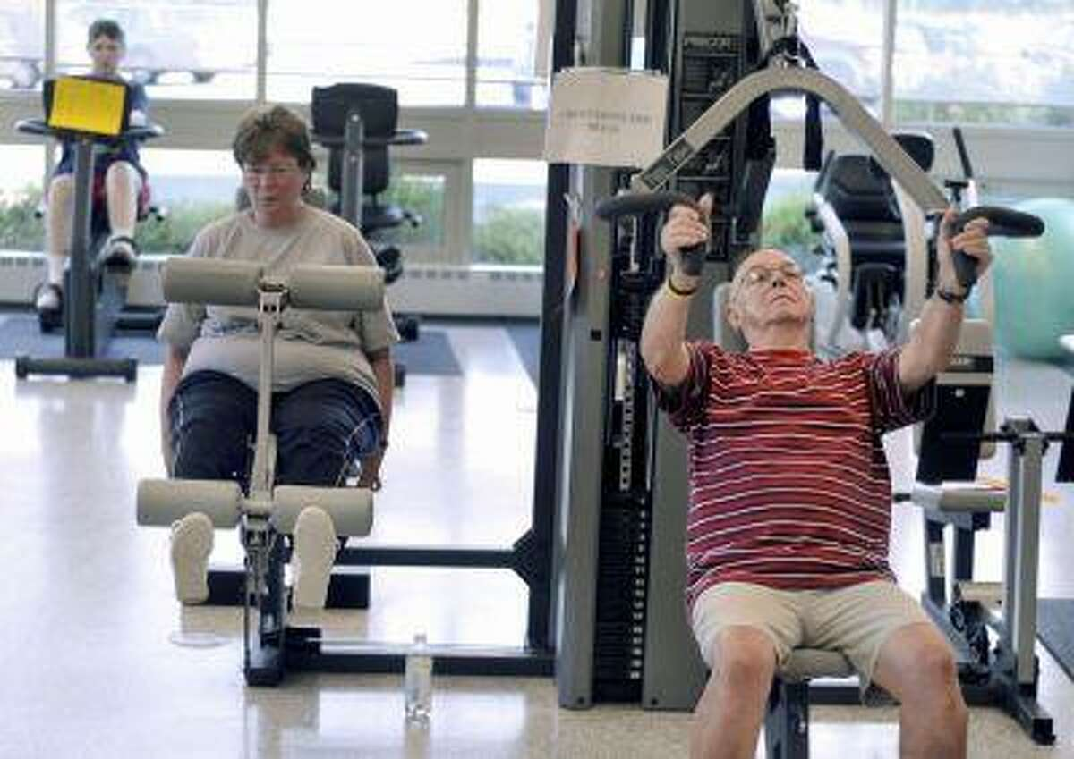 Rich Watton, right, Carol Roinson, center, and Janice Howell, back left, exercise in the gym at the Enfield Senior Center in Enfield, Conn., Aug. 13, 2008.