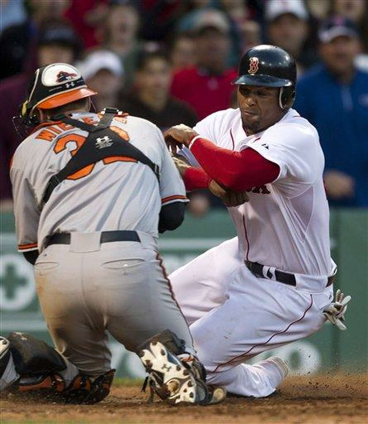 Boston Red Sox's Marlon Byrd, right, is tagged out at home by Baltimore Orioles catcher Matt Wieters, left, in the 16th inning of a baseball game at Fenway Park, in Boston, Sunday, May 6, 2012. The Orioles defeated the Red Sox 9-6 in 17 innings. (AP Photo/Steven Senne)