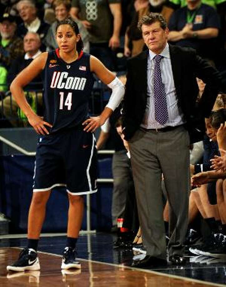 ASSOCIATED PRESS Connecticut guard Bria Hartley, left, stands with coach Geno Auriemma in the closing minutes of the second half of Saturday's game against Notre Dame in South Bend, Ind. Connecticut loss 74-67 in overtime.