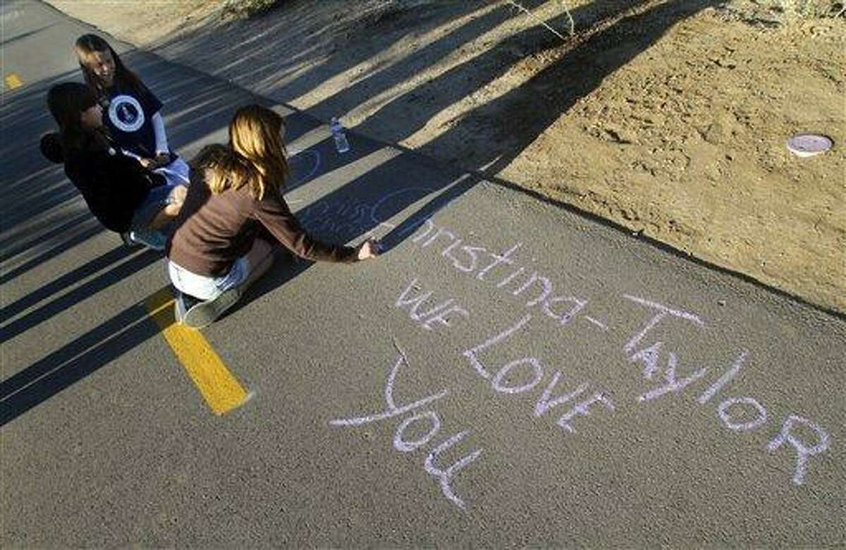 Jamie Stone, 10, a classmate of shooting victim Christina-Taylor Green writes a message on the path at the Christina-Taylor Green Memorial River Park on Saturday in Tucson, Ariz. The Beyond coalition, which is made up of individuals and Southern Arizona groups, held a series of events commemorating the Jan. 8, 2011 shootings by celebrating the spirit of togetherness Tucson residents felt in the days and months after the tragic event.