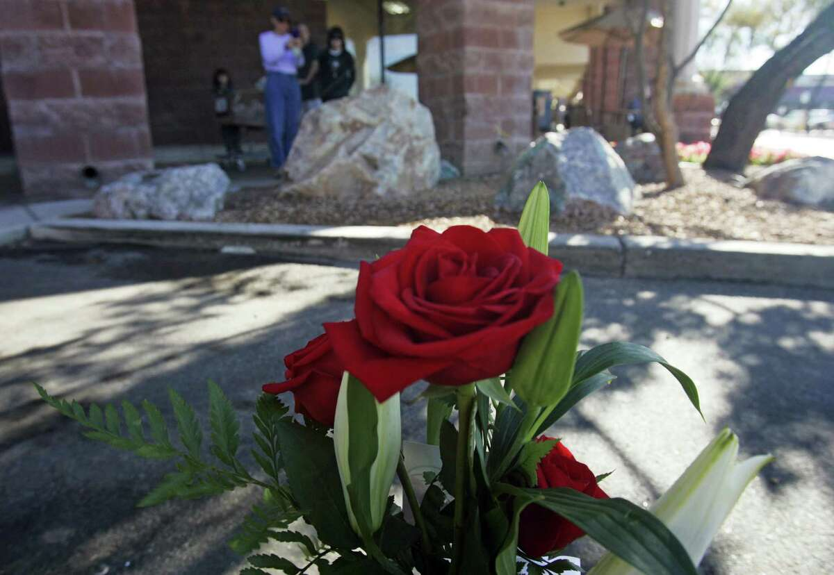 People gaze at a small memorial plaque on a rock at the Safeway market Saturday to commemorate the victims of the mass shooting on Jan. 8, 2011, in Tucson, Ariz. The one-year anniversary of the shooting of Rep. Gabrielle Giffords in the parking lot of the grocery store is Sunday. Arizona is marking the event with a series of events, including community-wide bell-ringing at the moment of the attack, speeches on behalf of the victims, and an evening candlelight vigil that Giffords will attend. Associated Press