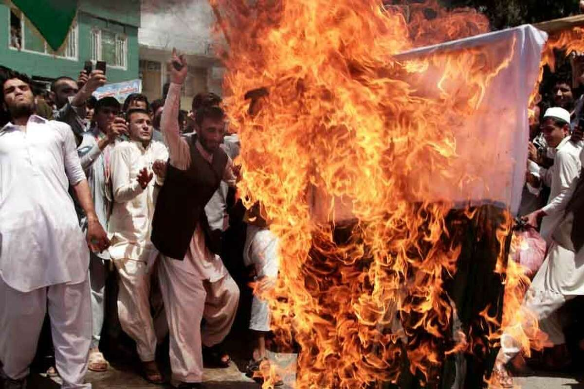 """Afghans chanting """"death to Pakistan"""" burn a Pakistani flag during a demonstration in Asad Abad, Kunar province, east of Kabul, Afghanistan, Tuesday, May 14, 2013. Relations between Afghanistan and Pakistan have been severely strained in recent months and the mountainous region in eastern Afghanistan has seen acrimonious exchanges of fire between the two sides over the demarcation of their border. (AP Photo/Rahmat Gul)"""
