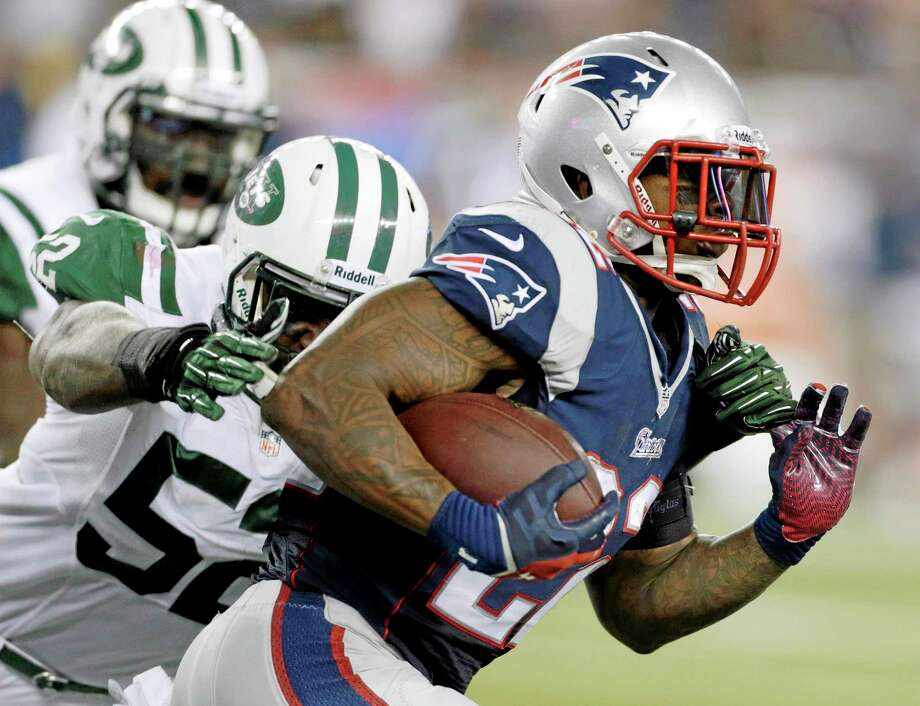 Patriots running back Stevan Ridley (22) runs past New York Jets inside linebacker David Harris last Thursday. Photo: Charles Krupa — The Associated Press  / AP