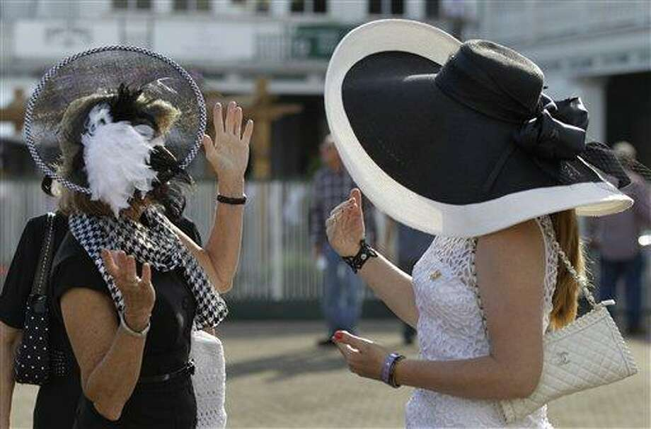 Dawn Paden, left, from Mountain Home, Ark., chats Saturday with Carrie Cooke, Louisville, Ky., before the 138th Kentucky Derby horse race at Churchill Downs in Louisville. Associated Press Photo: AP / AP