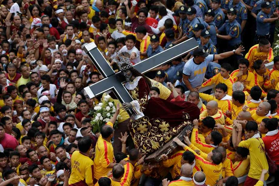 Catholic devotees jostle to get closer to the centuries-old image of the Black Nazarene in a raucous celebration on its feast day Wednesday, Jan. 9, 2013 in Manila, Philippines. The annual procession by hundreds of thousands of devotees is now becoming to be a tourist attraction. (AP Photo/Bullit Marquez) Photo: ASSOCIATED PRESS / AP2013