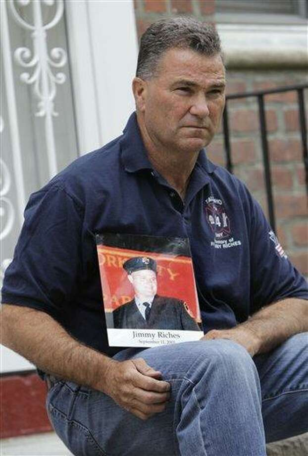 Retired firefighter Jim Riches poses for a picture with a photograph of his late son near his home in New York Thursday. Riches, whose son was killed during the 2001 terrorist attacks on the World Trade Center, was scheduled to be among those to watch the arraignment of Khalid Sheikh Mohammed. The arraignment of the self-proclaimed mastermind of the Sept. 11 terror attacks and four other Guantanamo Bay prisoners will be broadcast to only six sites at four military bases in the U.S. Northeast, a Pentagon spokesman said Monday.  Associated Press Photo: AP / AP