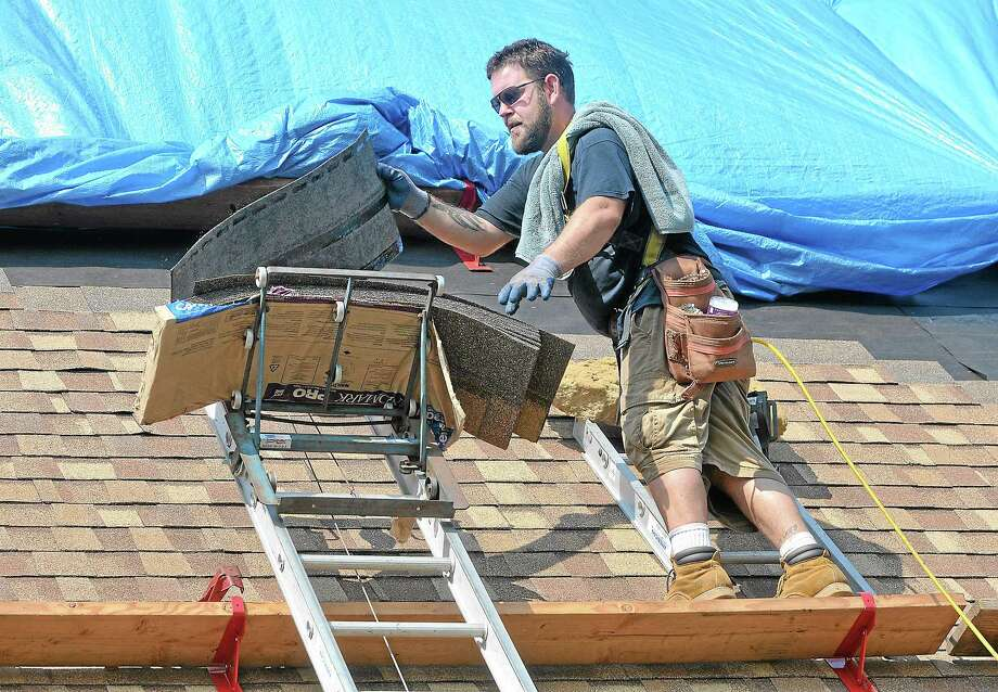Vernon roofer Brian Reilly works on a 90 degree September day replacing the shingles on the roof of Grace Lutheran Church on Randolph Road in Middletown. The team of roofers contracted by Neil Jones Improvements of Durham started replacing the 6,000 square foot job Tuesday and hope to have it completed by the end of the week or early next week at the latest. Catherine Avalone - The Middletown Press Photo: Catherine Avalone — The Middletown Press / TheMiddletownPress