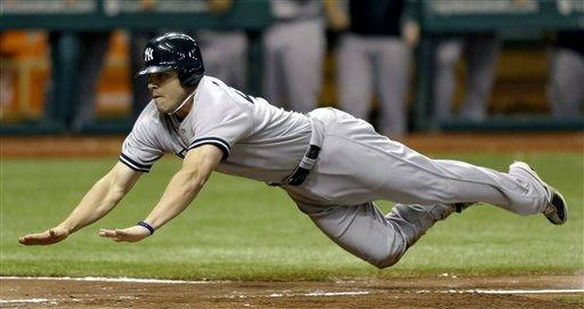 New York Yankees' Steve Pearce dives towards home plate scoring on a fielder's choice by teammate Derek Jeter and an error by Tampa Bay Rays second baseman Elliot Johnson during the seventh inning of a baseball game, Wednesday, Sept. 5, 2012, in St. Petersburg, Fla. (AP Photo/Chris O'Meara)