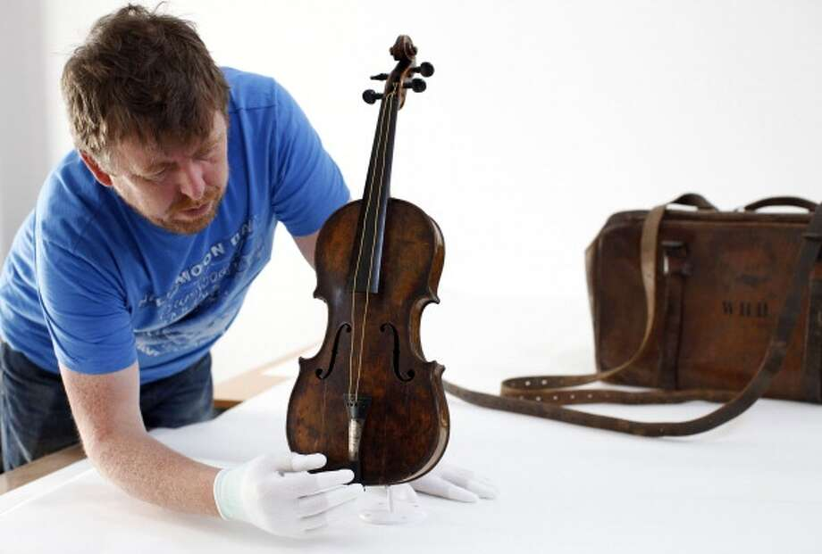 The violin played by bandmaster Wallace Hartley during the final moments before the sinking of the Titanic is displayed by conservator Sean Madden at his studio in Lurgan, Northern Ireland, on September 16, 2013, before going on public display at the Titanic Belfast. The Violin, which was owned by Titanic band leader Wallace Hartley, was recovered along with his body 10 days after he and other band members played to calm passengers on the deck of the stricken ship after it hit an iceberg on its maiden voyage. The instrument bears a engraved message from the musicians fiance that reads: For Wallace, on the occasion of our engagement. From Maria. AFP PHOTO/ PETER MUHLY        (Photo credit should read PETER MUHLY/AFP/Getty Images) Photo: AFP/Getty Images / 2013 AFP
