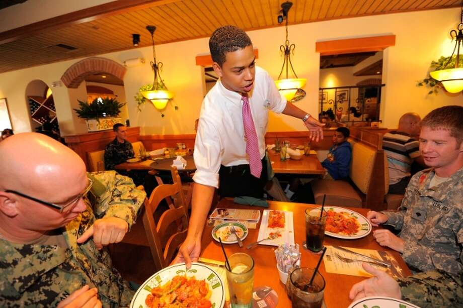 IMAGE DISTRIBUTED FOR DARDEN- A group of veterans celebrate Veterans Day with a free meal at the Olive Garden restaurant in Kissimmee, Fla. Olive Garden, Red Lobster and LongHorn Steakhouse are saluting those who serve our country by providing a variety of free menu items to veterans and active-duty military on Sunday, Nov. 11, 2012. (Scott A. Miller/AP Images for Darden) Photo: AP IMAGES FOR DARDEN / AP2012