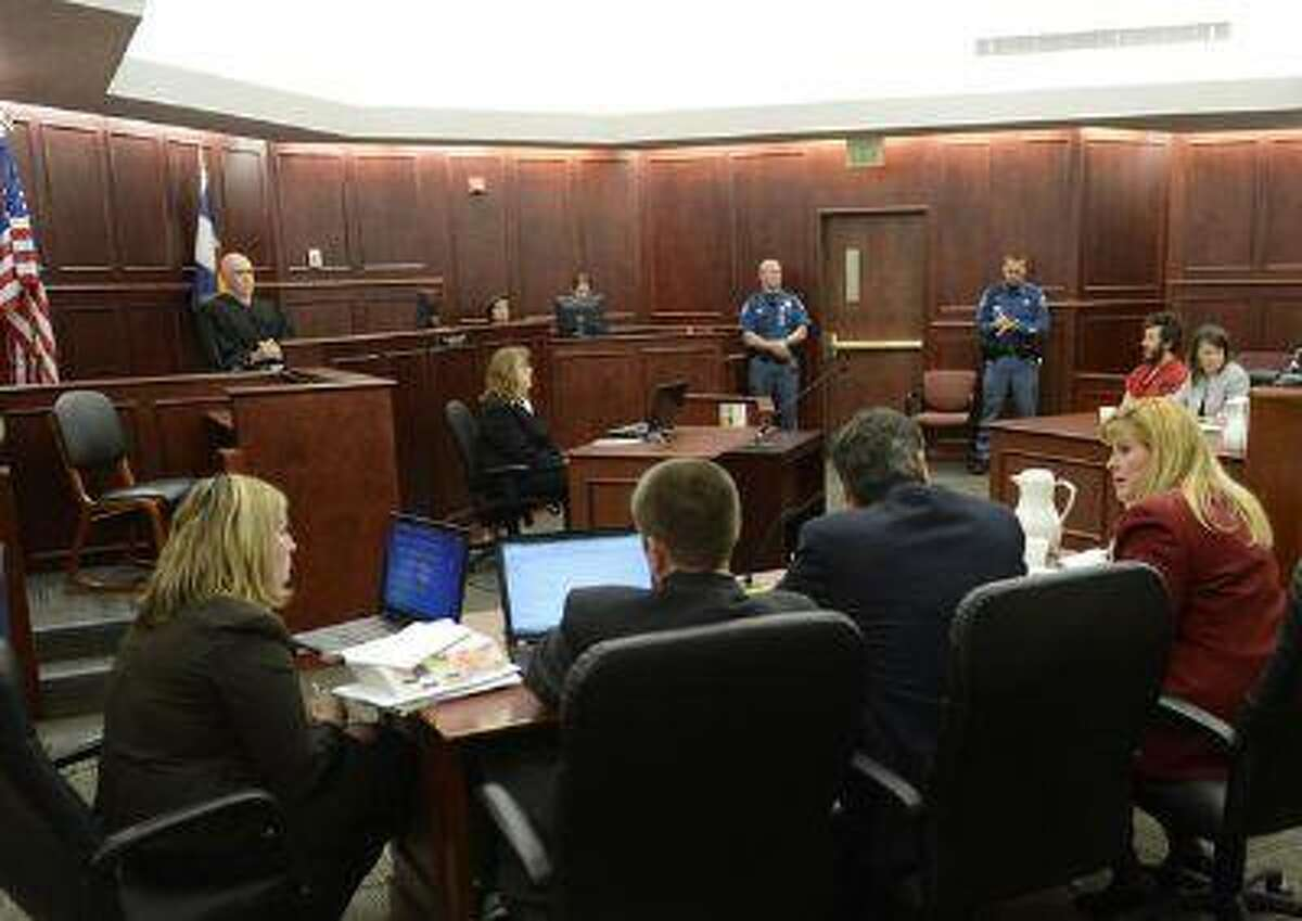 Prosecutor Karen Pearson, dressed in red suit, and the prosecution team at their table during the proceedings where District Court Judge William Sylvester entered a not guilty plea on behalf of James Holmes on March 12, 2013. (RJ Sangosti/The Denver Post file)