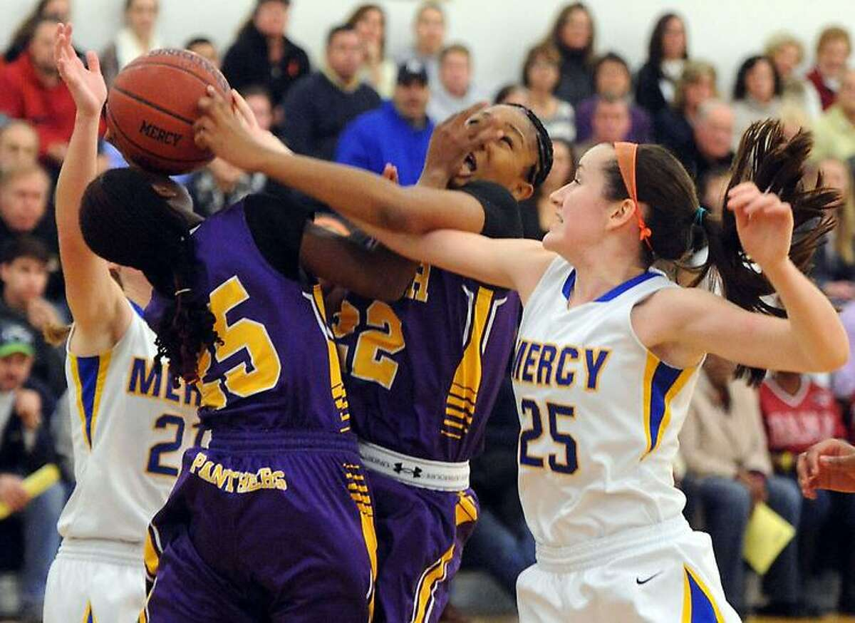 Career at Mercy, girls basketball. Mercy's Sheena Landy left and Maura Fitzpatrick right, and Career's Alyssa Alston (25) and Tanaya Atkinson (22) struggle for control. Mara Lavitt/New Haven Register1/9/13
