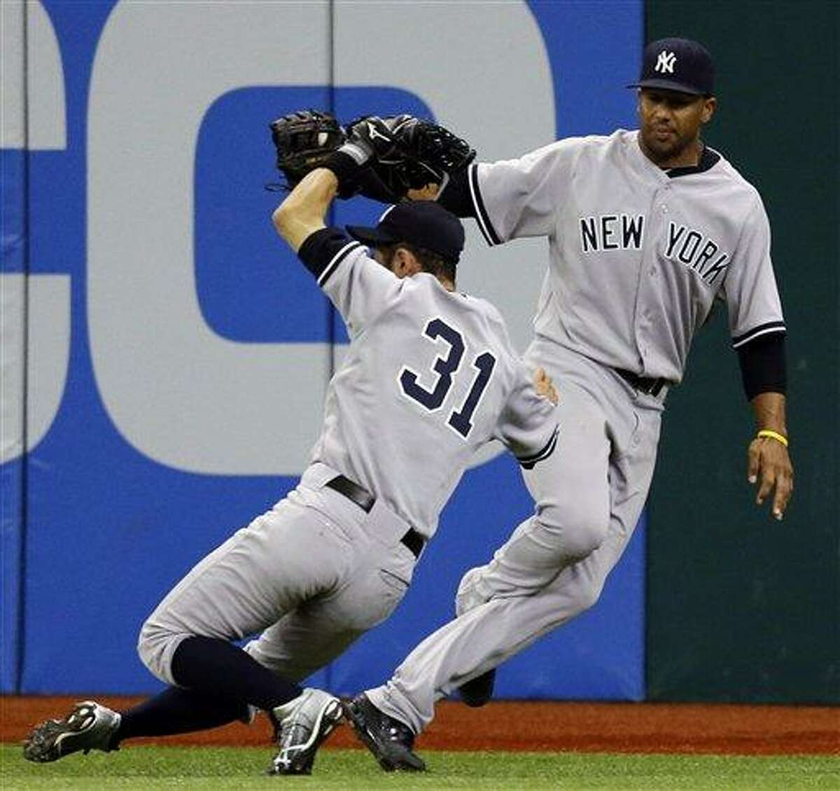 New York Yankees center fielder Chris Dickerson, right, and right fielder Ichiro Suzuki, of Japan, collide chasing an eighth-inning fly out by Tampa Bay Rays' Ben Francisco during a baseball game, Monday, Sept. 3, 2012, in St. Petersburg, Fla. Disckerson eventually made the catch. The Rays won 4-3. (AP Photo/Chris O'Meara)