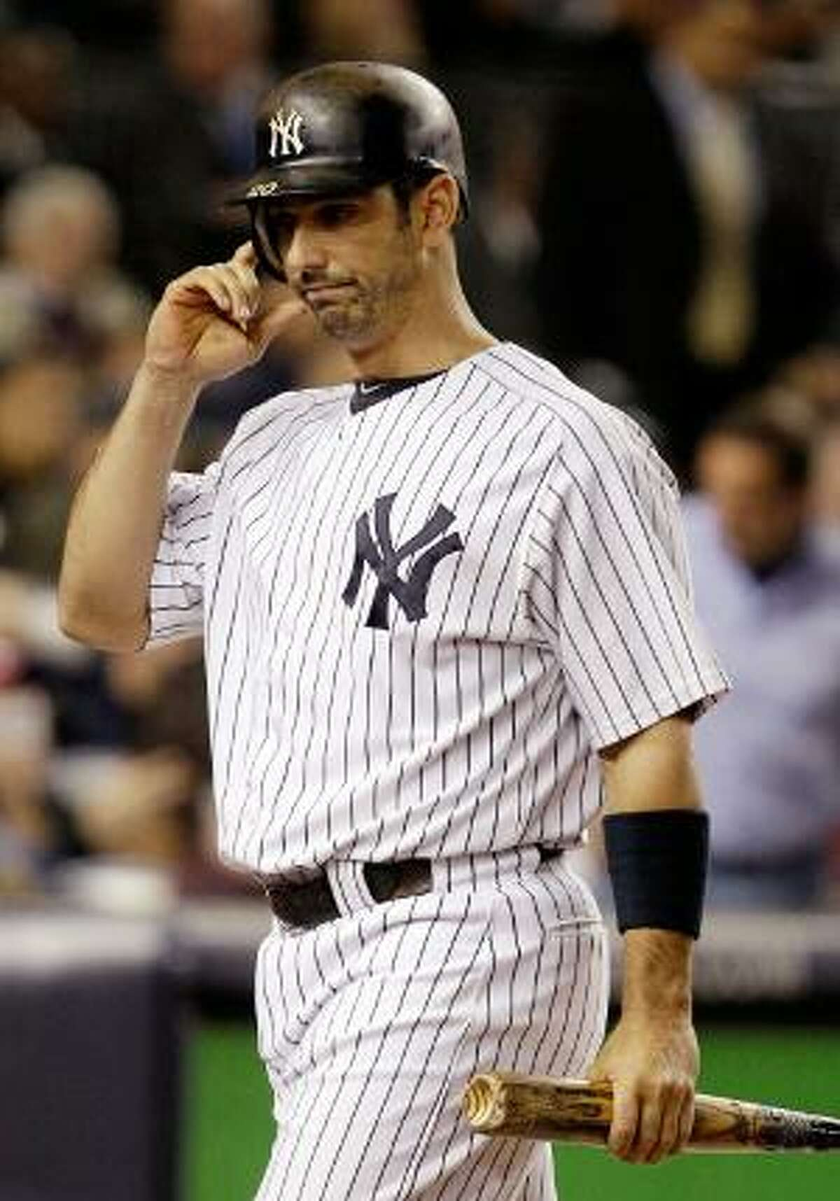 ASSOCIATED PRESS In this Oct. 6, 2011, file photo, New York Yankees designated hitter Jorge Posada prepares to remove his batting helmet after striking out in his final at bat in Game 5 of the American League Division Series in New York. A source told the AP that Possda plans to announce his retirement this month.