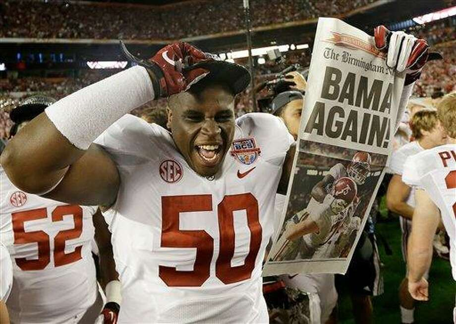 Alabama defensive lineman Alphonse Taylor (50) holds up a newspaper after the BCS National Championship college football game Monday, Jan. 7, 2013, in Miami. Alabama won 42-14. (AP Photo/David J. Phillip) Photo: ASSOCIATED PRESS / AP2013